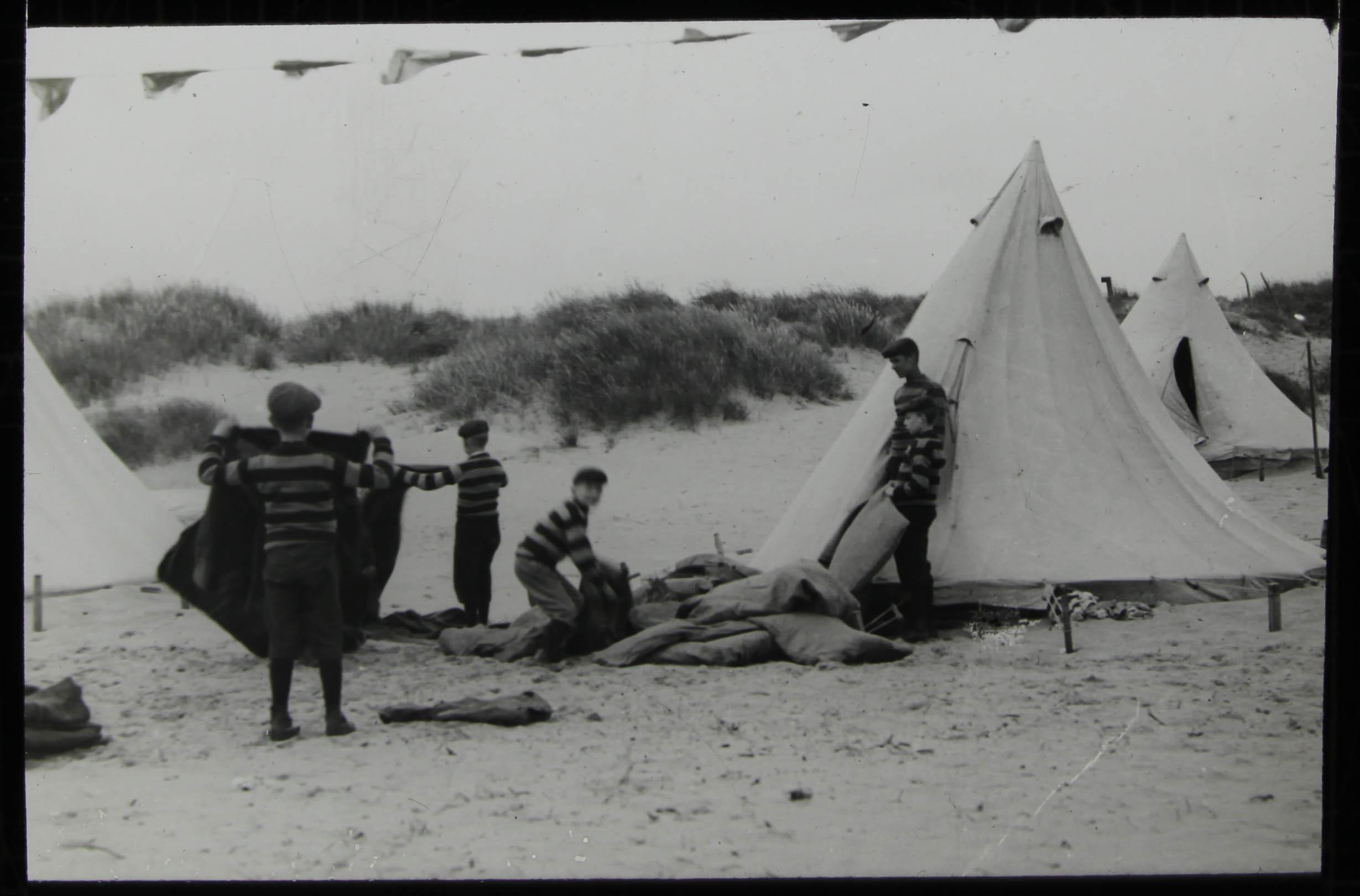 Boys pitching tents on the dunes -